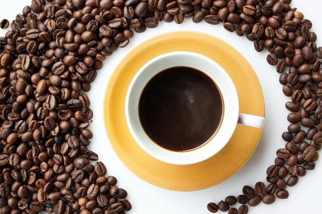 コーヒーカップの周りを囲うコーヒー豆