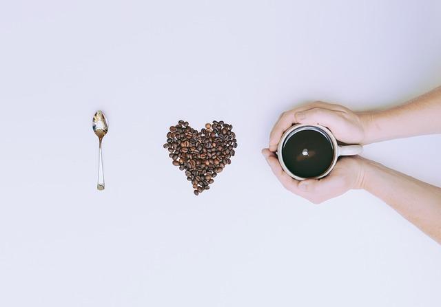 ハートに並べたコーヒー豆と手で覆ったホットコーヒー