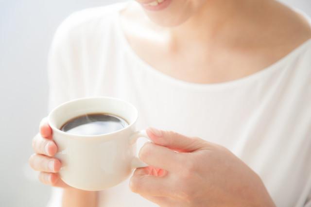 コーヒーを飲む白いシャツの女性